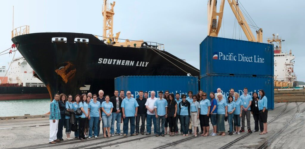 Group of people in front of ship and shipping containers